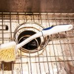 Wet stainless steel sink with garbage disposal and wire rack with scrub brush laying on it